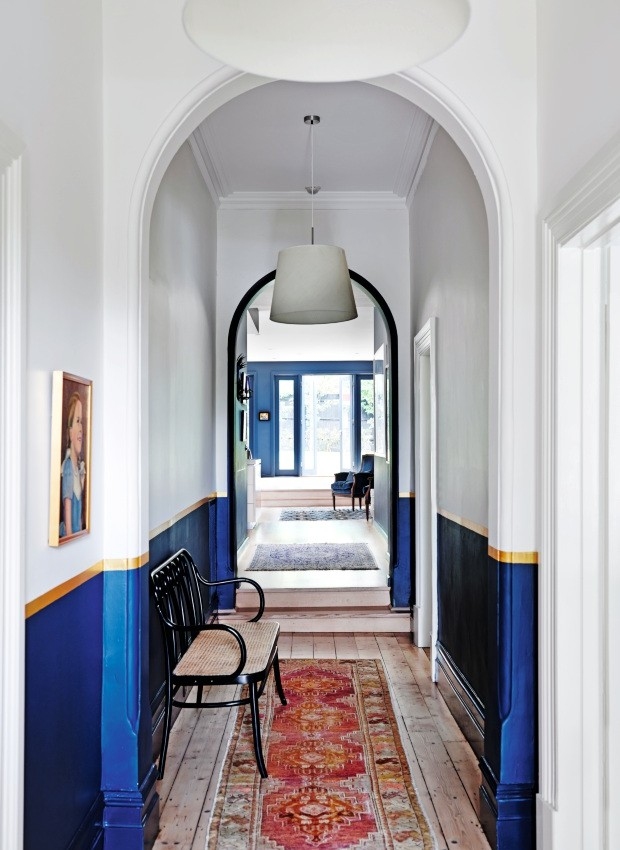 Corredor. O azul se estendeu para a passagem que liga os fundos da casa aos quartos. A parede foi pintada até a metade. Acima há uma faixa dourada, em sintonia perfeita com a cor da moldura do quadro (Foto: Lisa Cohen / Living Inside)