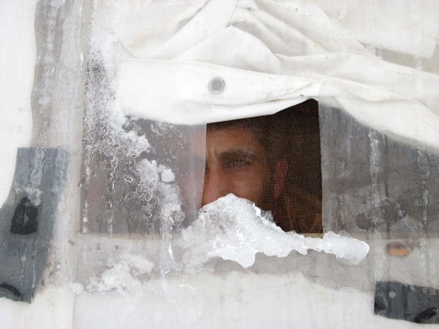 Refugiado sírio observa a neve da janela de sua barraca em um campo na cidade libanesa de Arsal, na quarta (7) (Foto: AFP Photo/Wissam Al-Omor)