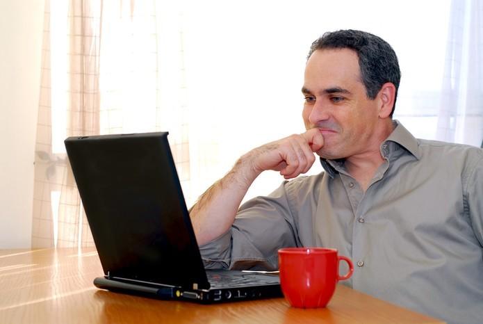 Homem olhando para o computador satisfeito (Foto: Pond5)