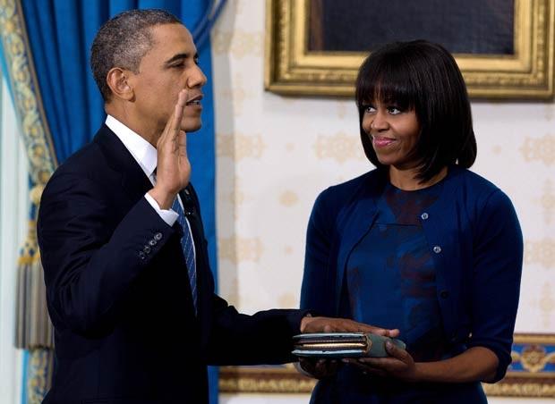 Observado pela primeira-dama Michelle, Obama presta juramento neste domingo (20) na Casa Branca (Foto: AP)