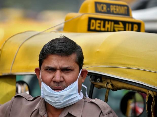 Motorista de auto-riquixá usa máscara para se proteger da poluição  (Foto: Reuters/Cathal McNaughton)