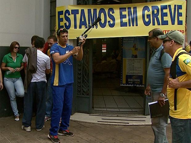 Servidor usa buzina para chamar a atenção das pessoas na porta da agência (Foto: Ronaldo Gomes/EPTV)