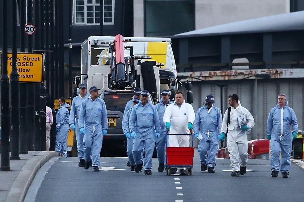 Peritos trabalham na London Bridge neste domingo (4) enquanto van branca usada no ataque é rebocada (Foto: REUTERS/Neil Hall)