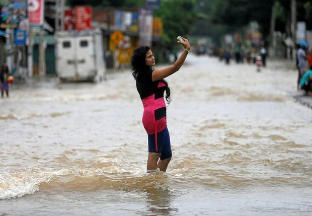 Apesar do caos que as fortes chuvas provocaram no Sri Lanka, jovem fez selfie no meio de rua inundada (Foto: Dinuka Liyanawatte/Reuters)