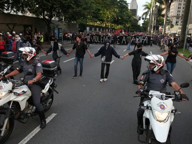 Mascarados fazem cordão em frente à manifestação, que segue pacífica (Foto: Marcelo Brandt/G1)