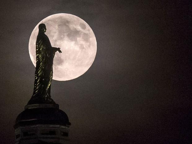 Lua vista sobre a estátua da Virgem Maria no topo da Universidade de Notre Dame, nos Estados Unidos (Foto: Robert Franklin/AP)