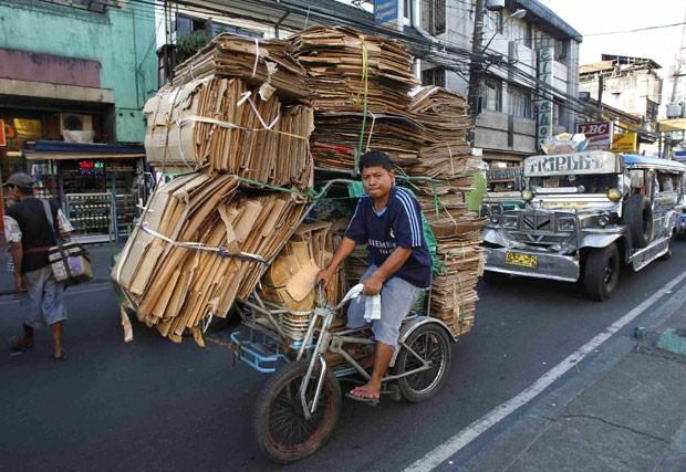 Homem foi flagrado nesta quarta-feira (30) dirigindo uma bicicleta superlotada com papelão em rua de Manila, nas Filipinas (Foto: Romeo Ranoco/Reuters)
