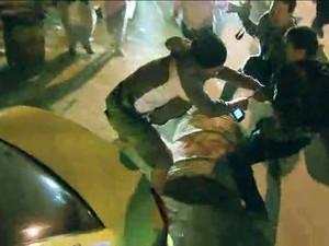 Fotógrafo é agredido durante soltura de manifestantes (Foto: Reprodução/GloboNews)