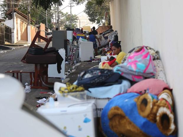 Mulher alimenta bebê enquanto moradores cuidam de seus pertences amontoados em uma calçada na manhã seguinte ao incêndio na favela conhecida como Buraco Quente, no Campo Belo, em São Paulo. Cerca de 600 famílias ficaram desalojadas (Foto: Renato S. Cerqueira/Futura Press/Estadão Conteúdo)