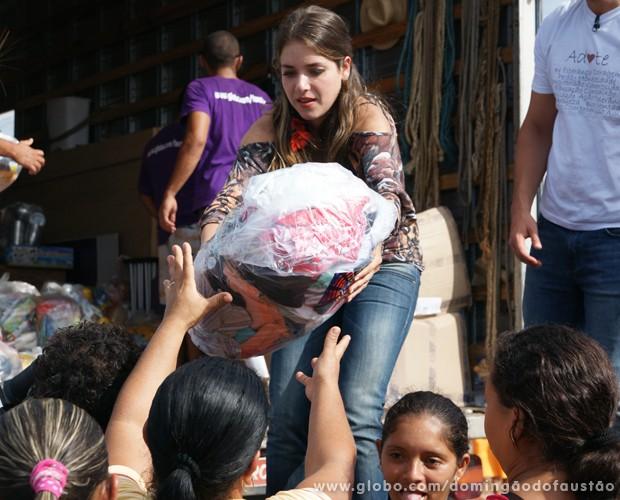 Monique Alfradique distribui roupas para as pessoas (Foto: Domingão do Faustão / TV Globo)