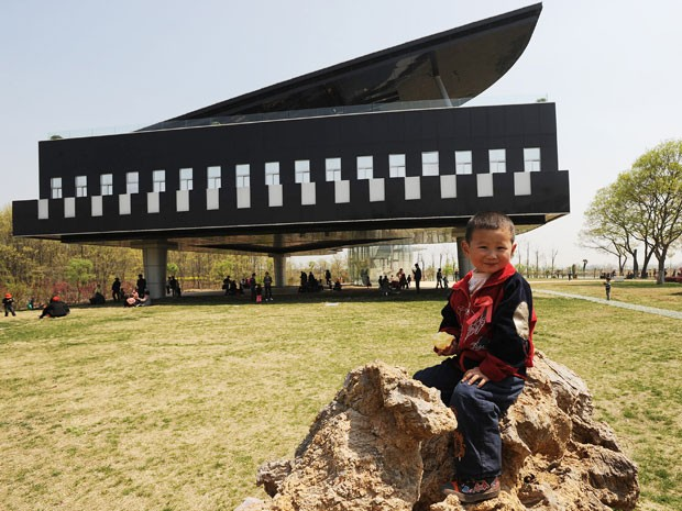 Criança posa em frente à parte de trás do Urban Planning Exhibition Hall, prédio em forma de piano e violino na China (Foto: STR/AFP)