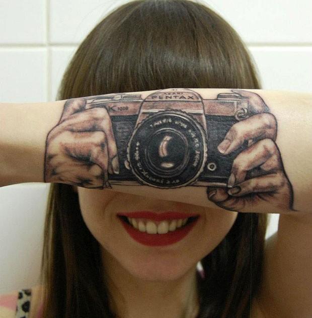 Jovem parece segurar câmera fotográfica ao exibir tatuagem (Foto: Reprodução)