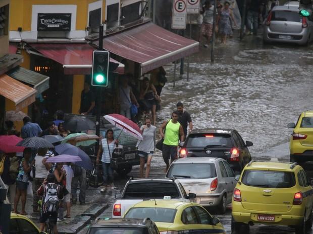 Pedestres tentam atravessar locais alagados no Centro (Foto: Rodrigo Gorosito/ G1)