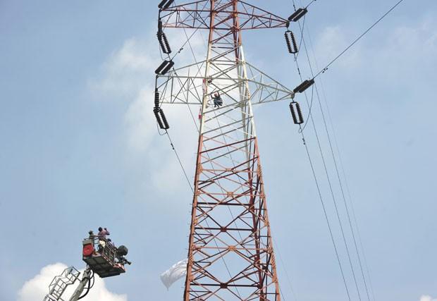Homem subiu em torre de alta tensão para protestar (Foto: Adek Berry/AFP)