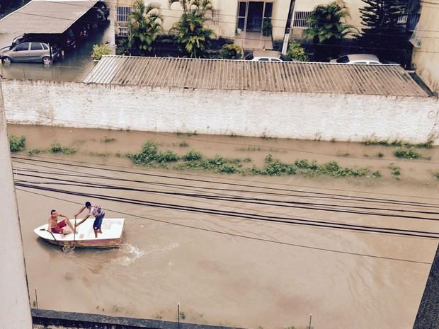Moradores improvisam barco para poder atravessar rua em Candeias, em Jaboatão dos Guararapes (Foto: Ewertton Santos / WhatsApp)