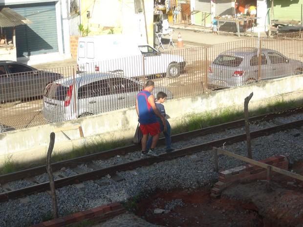 Pai e filho ignoram os riscos e andam pelo trilho do trem e VLT (Foto: Lucas Leite/G1)