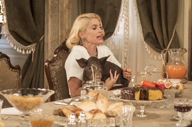 Flávia Alessandra em cena de Êta Mundo Bom com a porquinha Nina no colo (Foto: Globo/João Cotta)