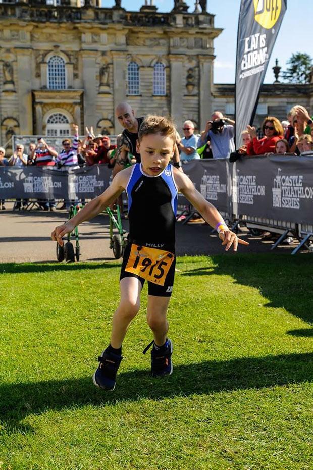 Bailey Matthews, de 8 anos, termina a prova de triatlo: paralisia cerebral não foi obstáculo para garoto da Inglaterra  (Foto: Reprodução/Facebook/Castle Triathlon Series)