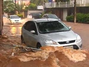Carros ficaram parados em trehos alagados na capital (Foto: Reprodução/TV Anhanguera)