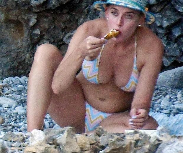 Gente como a gente! Katy Perry come coxa de frango em praia na Itália