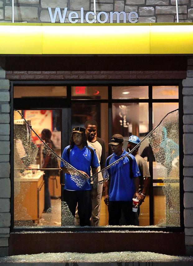 Funcionários observam os estragos na entrada de uma lanchonete McDonald's que teve vidros quebrados durante protesto reprimido pela polícia na noite de domingo (17) em Ferguson, Missouri (Foto: Robert Cohen/St. Louis Post-Dispatch/AP)