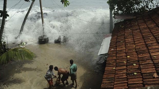Moradores da costa do Mar Arábico tentam colocar sacos de areia para proteger a casa no momento em que a água invade o quintal em Kochi, no estado indiano de Kerala. A monção sudoeste, crucial para a agricultura indiana, atingiu a região nesta terça (5). (Foto: AP)
