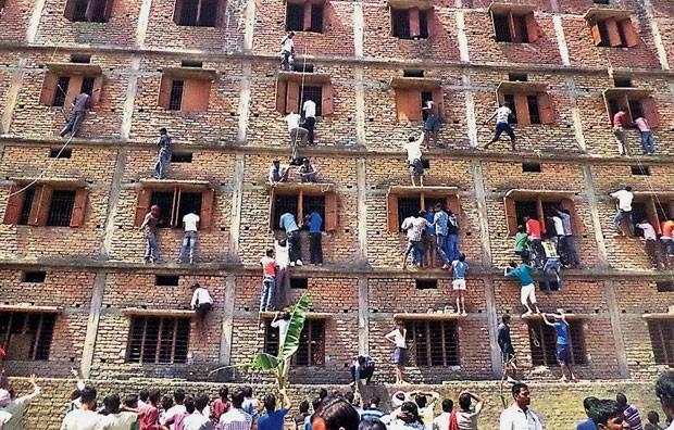 Pais escalam prédio de escola para ajudar filhos a colarem em prova (Foto: AP Photo/Press Trust of India)