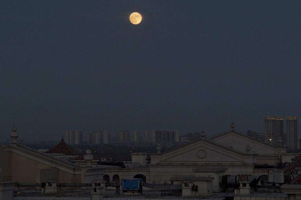 Superlua já aparece na China e perde um pouco do brilho entre a poluição   (Foto: Ng Han Guan/AP Photo)