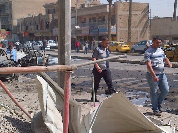 Policiais observam carro-bomba que explodiu neste domingo (30) em Karrada, em  Bagdá (Foto: AFP)