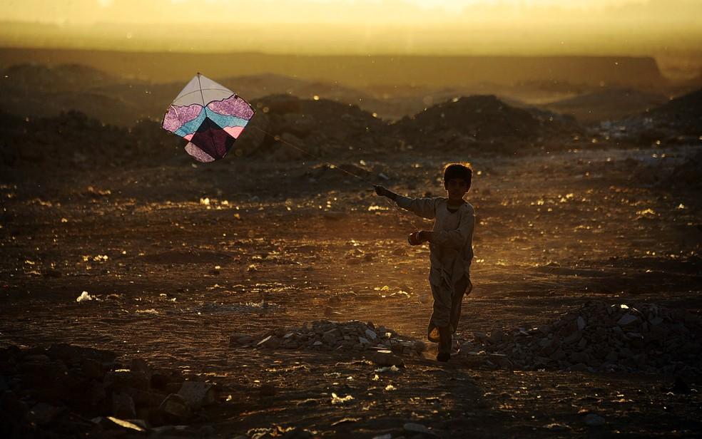 Criança brinca com uma pipa nos arredores de Herat, no Afeganistão (Foto: Aref Karimi / AFP Photo)