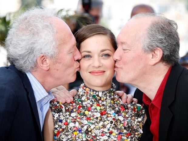 A atriz francesa Marion Cotillard recebe beijo dos irmãos Dardenne, Luc (à dir.) e Jean-Pierre (à esq.), durante apresentação do filme 'Deux jours, une nuit' no Festival de Cannes nesta terça-feira (20) (Foto: Valery Hache/AFP)