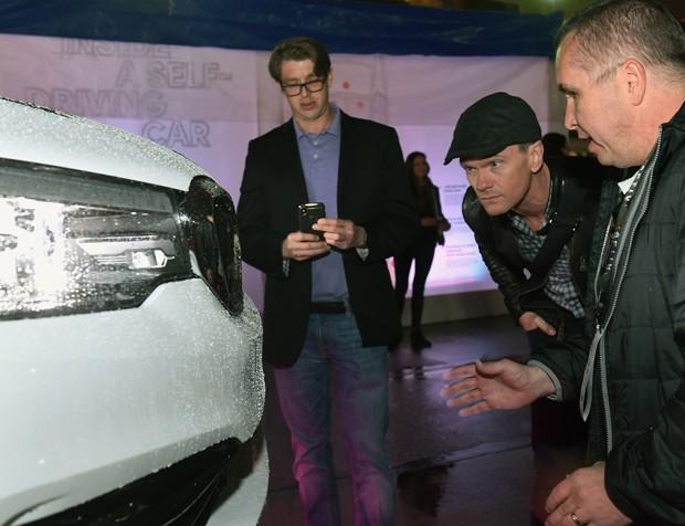 O ator Neil Patrick Harris e o diretor de engenharia Ron Szabo, da Aptiv, conferem um dos sensores que fazem parte do sistema do táxi autônomo da Lyft (Foto: Bryan Steffy/Getty Images)