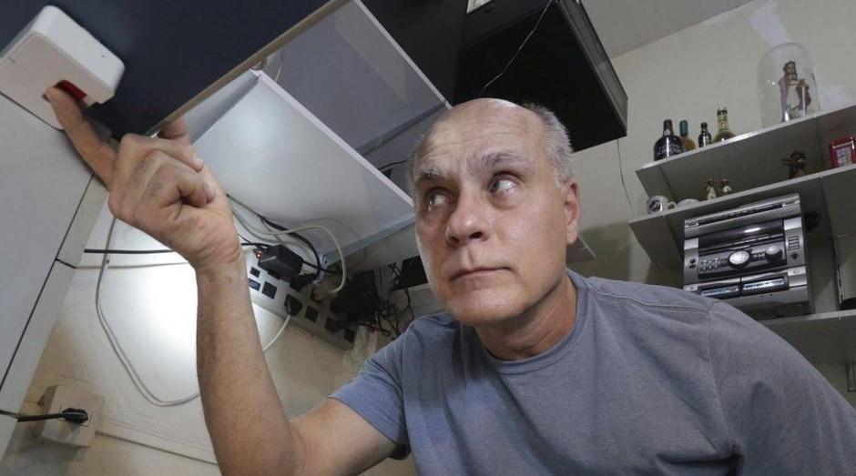 Osmar Alfena mostra o botão do pânico embaixo da mesa de seu escritório: ele tem mais dois dispositivos: um fica numa parede, e o outro é um controle de bolso (Foto: Agência O Globo)
