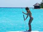 De biquíni, Carol Magalhães pratica stand up paddle