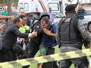 Mesmo após ser atingido por disparo de bala de borracha, homem tenta fugir, mas é contido por policiais (Foto: Vianey Bentes/TV Globo)