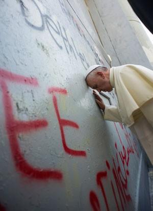 O Papa Francisco ora na barreira de segurança entre Israel e a Cisjordânia, neste domingo (25) (Foto: AFP/Osservatore Romano)