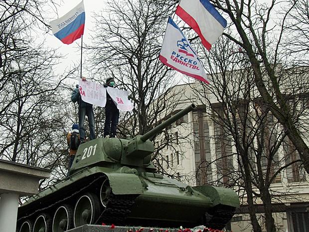 Grupo pró-Rússia sobre tanque soviético T-34 segura placa onde se lê 'Crimeia pela paz'  em frente ao Parlamento de Simferopol nesta sexta-feira (27). (Foto: Vasily Batanov/AFP)