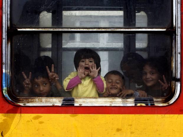 Crianças migrantes acenam da janela de um trem em direção à Sérvia, na Macedônia (Foto: Boris Grdanoski / AP)