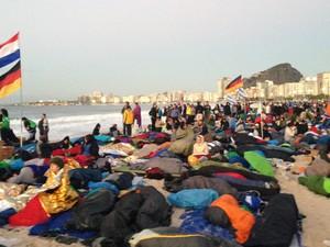 Peregrinos observam o amanhecer na praia de Copacabana após passarem a noite em vigília. (Foto: Eduardo Carvalho/G1)