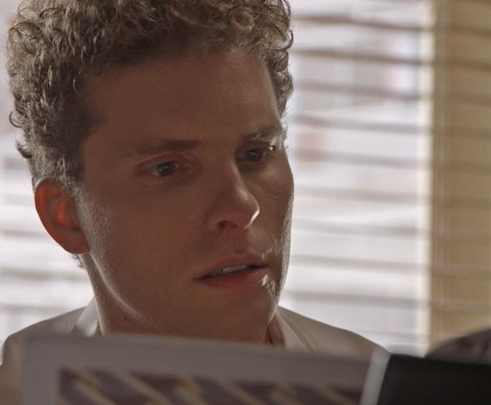 Vinícius fica chocado ao ver foto de Regina na revista (Foto: TV Globo)