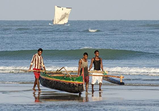 Jovens Vezo carregam uma canoa com estabilizador lateral, retirando-a do mar. (Foto: © Haroldo Castro/Época)