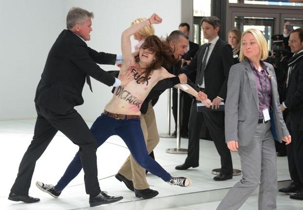 Mulher com os seios à mostra é barrada ao tentar se aproximar do presidente russo (Foto: Jochen Lübke/DPA/AFP)