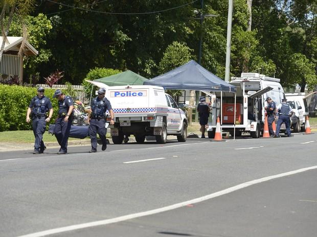 Policiais carregam corpo de criança achado em casa na Austrália (Foto: AP)