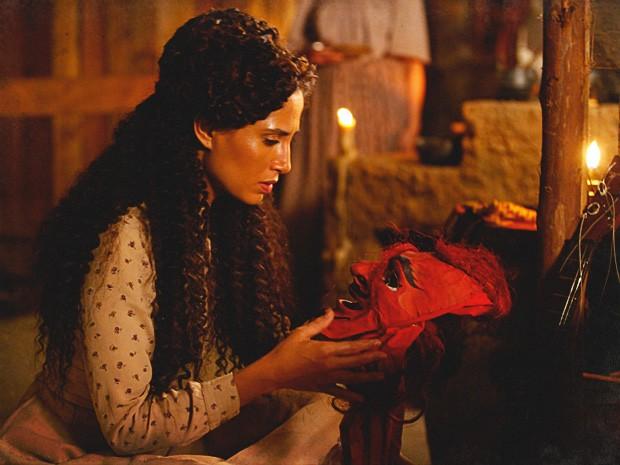 Isabel abre a trouxa de roupas de Zé Maria e encontra máscara de Carnaval (Foto: Lado a Lado / TV Globo)