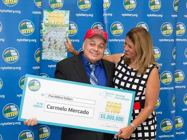 Carmelo Mercado posa com cheque simbólico de US$ 5 milhões, após ganhar na loteria em Nova York (Foto: Philip Kamrass/New York State Gaming Commission via AP)