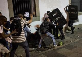 Manifestantes agridem PM na Assembleia do Rio, durante protesto dia 17 (Foto: Felipe Dana/AP)