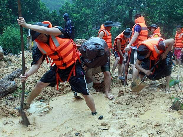 Equipes de resgate e voluntários escavam e reviram região de deslizamento à procura de desaparecidos após chuvas e deslizamentos de terra no norte do Vietnã (Foto: Vietnam News Agency / via AFP Photo)