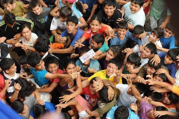 Crianças se empurram para pegar notas atiradas de igreja em Guarambaré, no Paraguai (Foto: Norberto Duarte / AFP)