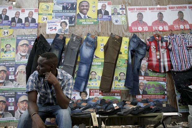 Vendedor de roupas coloca calças e camisas penduradas em frente aos cartazes da eleição presidencial haitiana, que acontece no domingo (25) (Foto: Jossy Ola/AP)