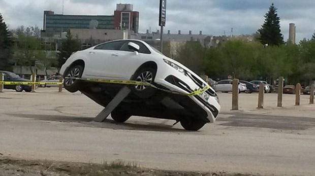 Canadense flagrou carro estacionado sobre barra de proteção em Winnipeg (Foto: Reprodução/Twitter/CBC Manitoba)